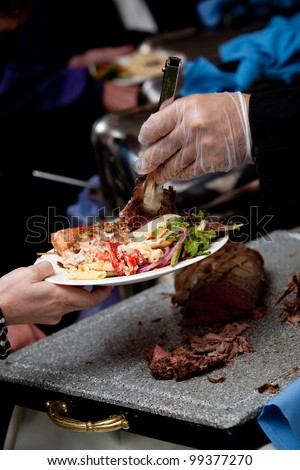 a gloved hand serving wedding food at a catered event - stock photo