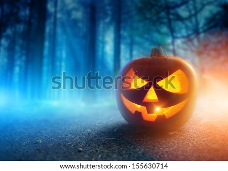 A glowing Jack O Lantern in a dark mist Forest on Halloween... - stock photo