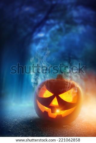 A glowing Jack O Lantern in adark mist Forest on Halloween... - stock photo