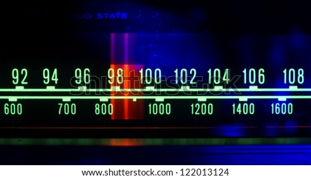 a glowing radio with the marker running through the different stations and frequencies - stock photo