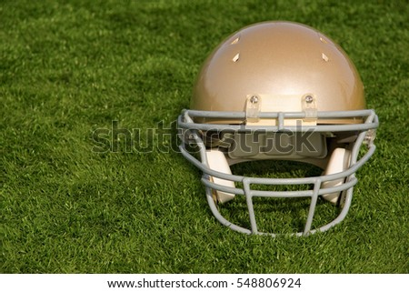 A gold American football helmet resting on turf