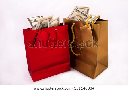 A gold and a red gift bag with dollars, isolated  - stock photo