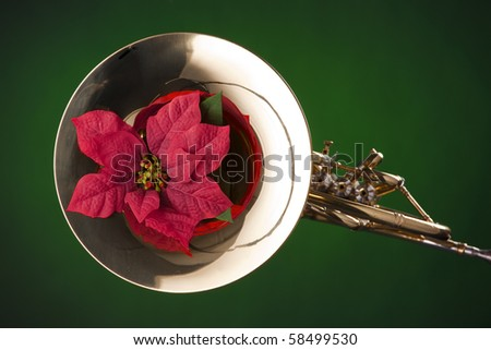 A gold brass French horn and red poinsettia flower isolated  against a spotlight green background. - stock photo