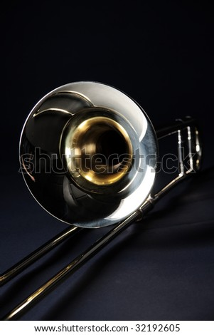 A gold brass trombone isolated against a black background in the vertical format. - stock photo