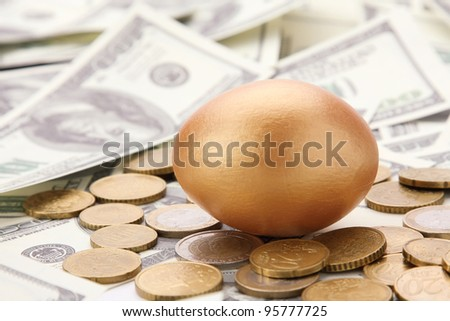 A gold egg lying on dollars and coins - stock photo