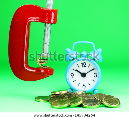 A Gold Euro Symbol in a red vice, with a blue clock resting on some gold coins, asking the question how far will the Euro be squeezed. - stock photo
