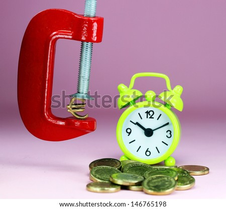 A Gold Euro Symbol in a red vice, with a green clock resting on some gold coins with a pastel purple background, asking the question how far will the Euro be squeezed. - stock photo