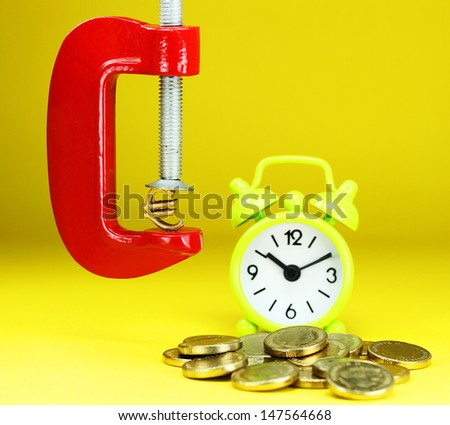 A Gold Euro Symbol in a red vice, with a green clock resting on some gold coins with a pastel yellow background, asking the question how far will the Euro be squeezed. - stock photo