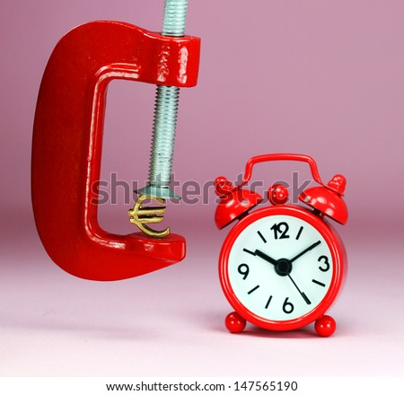 A Gold Euro Symbol in a red vice, with a red clock with a pastel pink background, asking the question how far will the Euro be squeezed. - stock photo