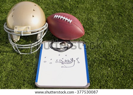 A gold helmet, football and clipboard on a field.