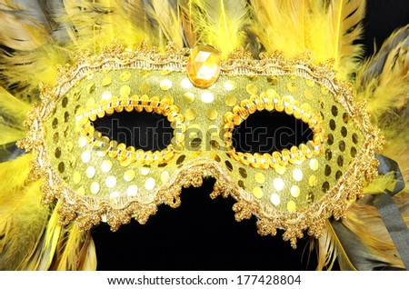 A gold Mardi Gras mask with gold and black feathers. - stock photo