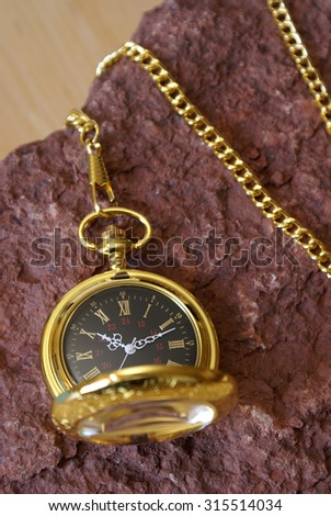 A gold pocket watch on a red sandstone. - stock photo