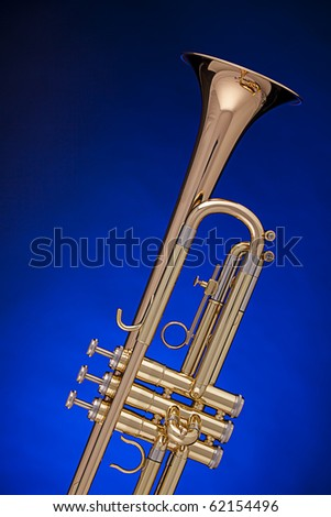 A gold professional trumpet isolated against a spotlight blue background with copy space.