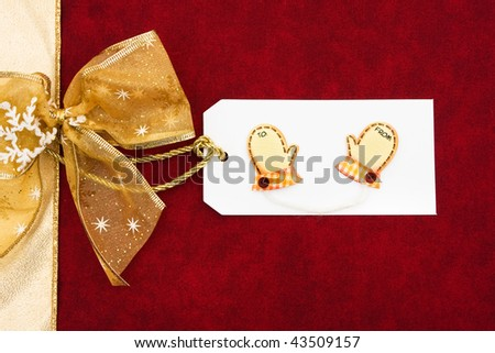 A gold ribbon bow sitting with a blank gift tag on a red background