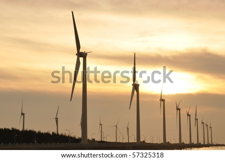 a gold sunset at the wind-power station - stock photo