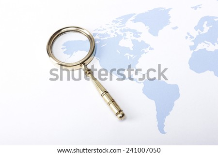 A gold vintage(classic, old) magnifier(reading glass) focus in alaska on the blue world map. - stock photo