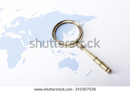 A gold vintage(classic, old) magnifier(reading glass) focus in korea, japan on the blue world map. - stock photo
