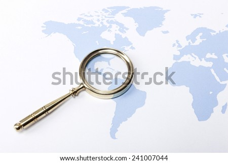 A gold vintage(classic, old) magnifier(reading glass) focus in mexico on the blue world map. - stock photo