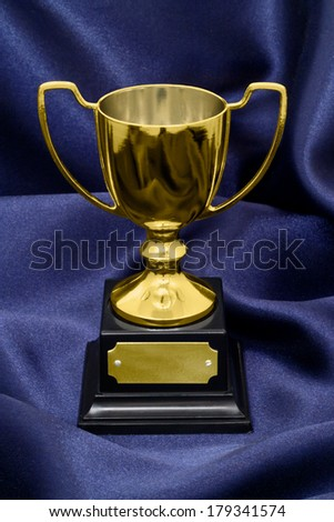 A Gold Winners trophy on a blue silk background great concept for achievement, success or winning a competition or award. - stock photo