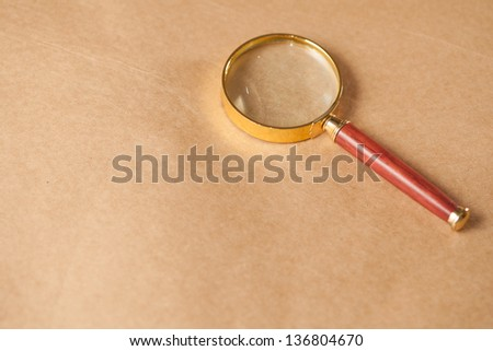 A golden and red magnifying glass on a brown paper background. - stock photo