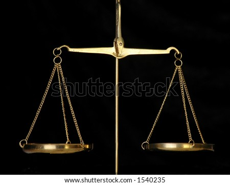 A golden balance scale against a black background. - stock photo