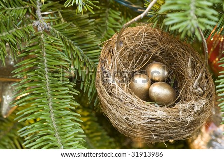 A golden bird's nest and eggs decorating the Christmas tree.
