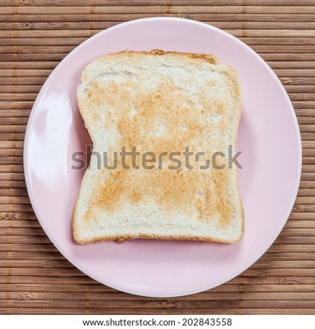A golden brown slice of toast on a pink plate with a bamboo background