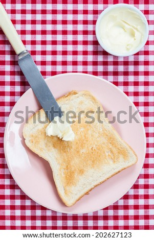 A golden brown slice of toast on a pink plate with butter ready to be spread