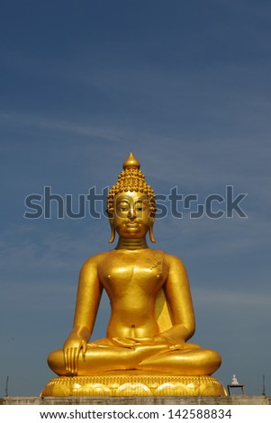 A golden buddha statue sits in peaceful meditation, Thailand