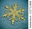 a golden christmas ornament with the shape of a snowflake on a blue textured background - stock photo