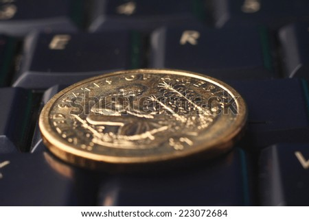 A golden coin on the keyboard - stock photo