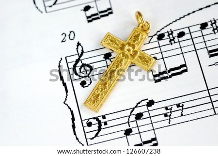 A golden cross on the top of a music sheet concept of religion - stock photo