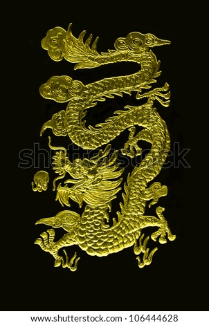 A golden dragon carving with black background - stock photo