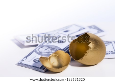 A golden egg cracked open sits in front of some money. - stock photo