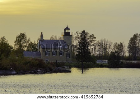 A Golden Hour Fall Shot of the Ontonagon Lighthouse in Michigan Looking Over Lake Superior - stock photo