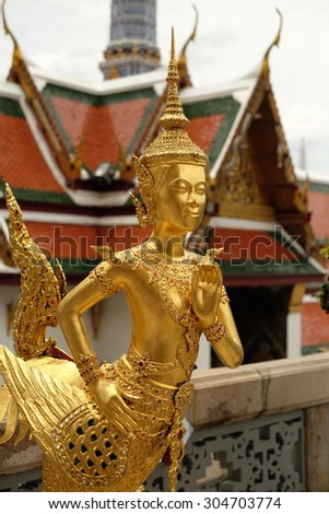 A Golden Kinnari statue att he Temple of the Emerald Buddha (Wat Phra Kaew) , Bangkok, Thailand - stock photo