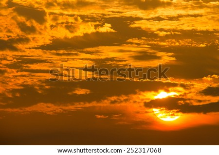 A golden orange sunset and a cloud filled sky. - stock photo