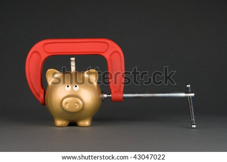 A golden piggy bank is being squeezed for its last dollar.  Image can be used for many financial inferences, including recession; savings; economy; retirement; investment and poverty.
