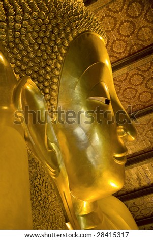 A golden reclining buddha statue at a Thai temple in Bangkok