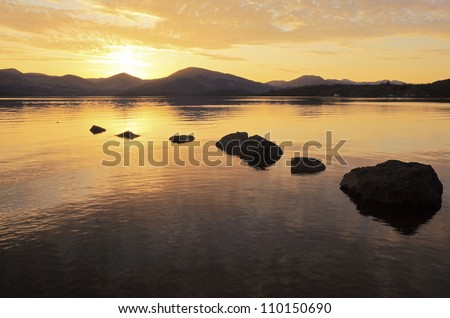 A golden Sunset at Milarrochy bay on the east bank shore of Loch Lomond, Scotland - stock photo