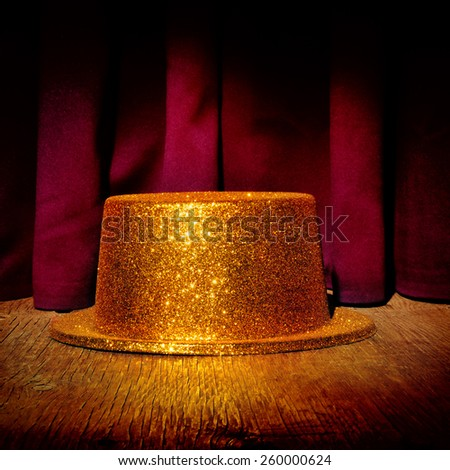 a golden top hat on a stage with the theater curtain in the background - stock photo