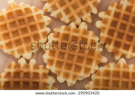 A golden waffle on wood background, top view.