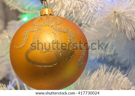 a golden xmass ball hanging at xmass tree - stock photo