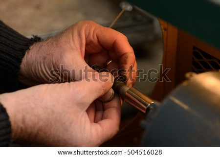 A goldsmith polishes the inside surface of a gold ring