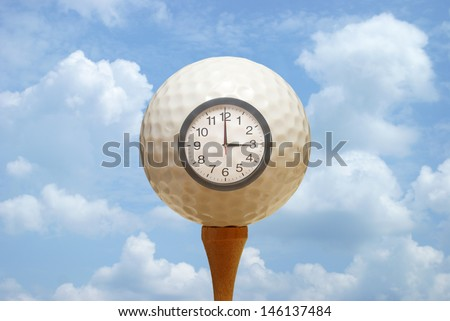 A golf ball and clock remind the golfer of their tee off. - stock photo