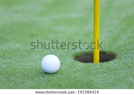 A golf ball extremely close to the hole. - stock photo