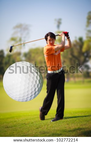 A golf ball just coming off the tee from a golfer in swing - stock photo