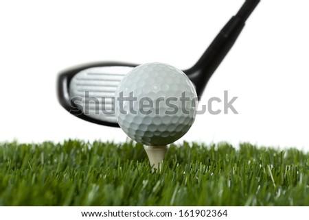 A golf ball on a tee ready to be hit by a golf club  - stock photo