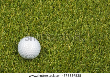 A Golf ball on course with green grass.