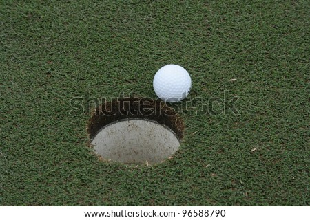 a golf ball on the edge of the cup